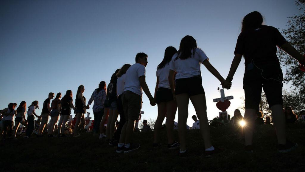 Des lycéens et leurs familles se tiennent la main autour d'un mémorial improvisé devant le lycée Marjory Stoneman Douglas, le 18 février 2018.