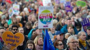 """Un manifestant brandit une pancarte """"Stop AfD"""" pendant une manifestation à Berlin dimanche 22 octobre."""