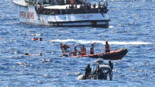 Migrantes rescatados por la embarcación española Open Arms se arrojan al mar para nadar hacia Lampedusa y son rescatados por la guardia costea italiana.