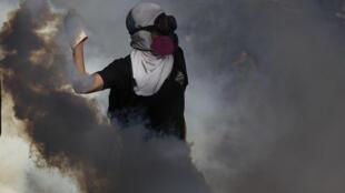 Un manifestante lanza una bombona de gas lacrimógeno a la policía antidisturbios durante una protesta contra el gobierno del presidente chileno Sebastián Piñera en Santiago, el 27 de diciembre de 2019.