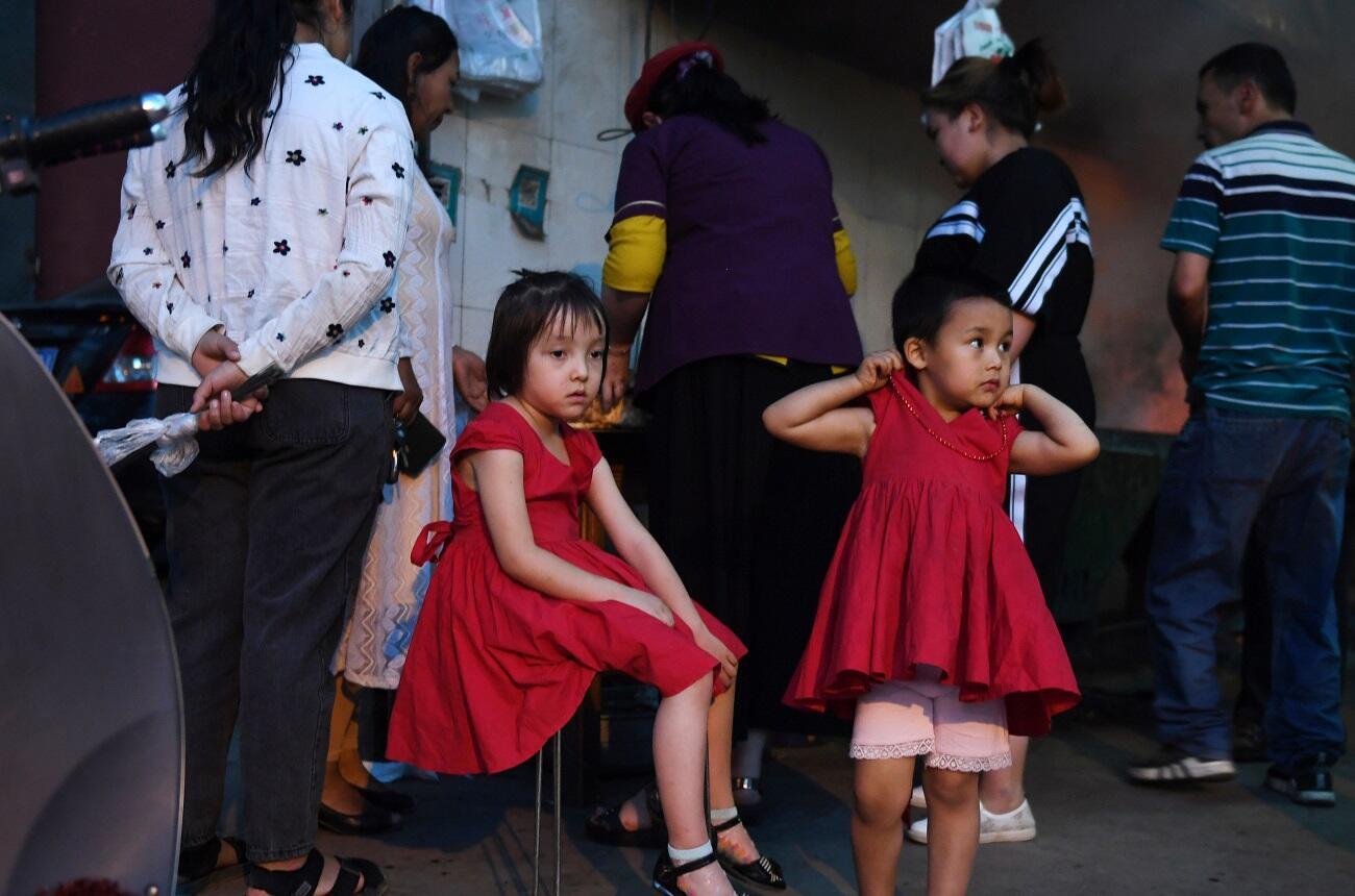 طفلتان من الأويغور تنتظران والديهما خارج مطعم في هوتان شمال غرب شينجيانغ بالصين، 31 مايو/أيار 2019.