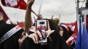 Una simpatizante del presidente Recep Tayyip Erdogan, con una imagen suya en la funda del teléfono móvil, toma fotografías en un mitin electoral del partido, el 17 de junio de 2018 en Estambul