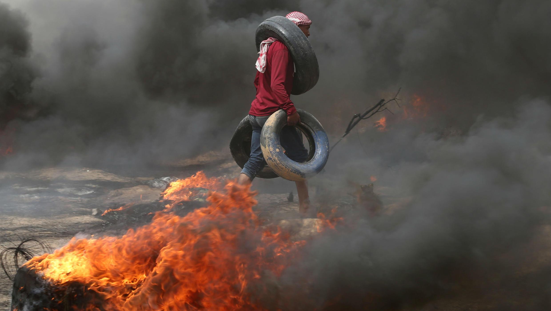 Manifestante palestino lleva neumáticos durante los enfrentamientos con las tropas israelíes.