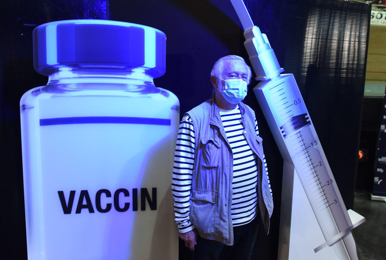 """Raymond Vericel pose pour une photo près de la sortie après sa vaccination. """"On croise des gamins dans notre escalier dont la classe avait été fermée en raison du Covid... c'est rassurant de se faire vacciner"""", affirme le retraité de 74 ans."""
