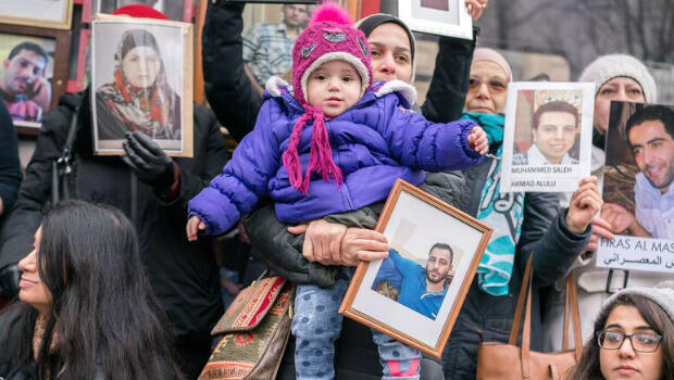 Families of the detained hold photos of their missing relatives