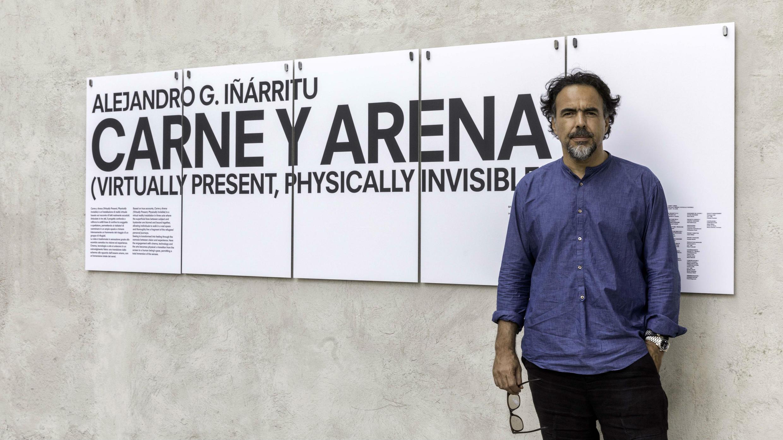 """El director Alejandro Iñárritu posa frente a la exposición """"Carne y Arena""""."""