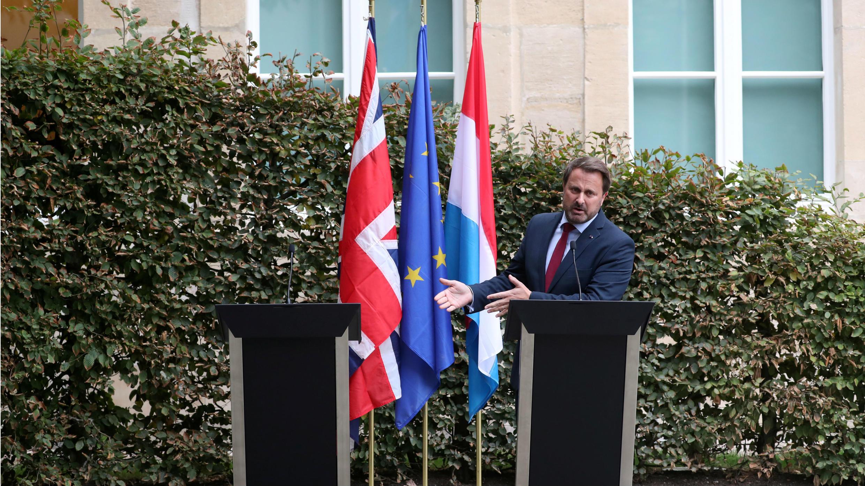 El primer ministro de Luxemburgo, Xavier Bettel, señala el atril vacío a su lado, en la ausencia del premier británico Boris Johnson.