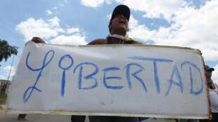 """امرأة تحمل لافتة كتب عليها """"الحرية"""" على الحدود بين فنزويلا والبرازيل، البرازيل-24 فبراير/شباط 2019."""