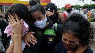 Familiares de una víctima de la COVID-19 que murió al comienzo de la pandemia en Ecuador, lloran mientras esperan los restos de su ser querido recién identificado en la ciudad portuaria de Guayaquil, el 16 de julio de 2020.