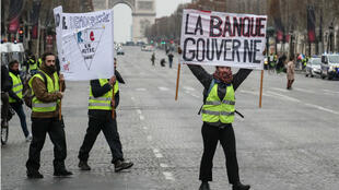 Un Gilet jaune tient une pancarte anti-banque lors de la manifestation du 15 décembre aux Champs-Élysées, à Paris.