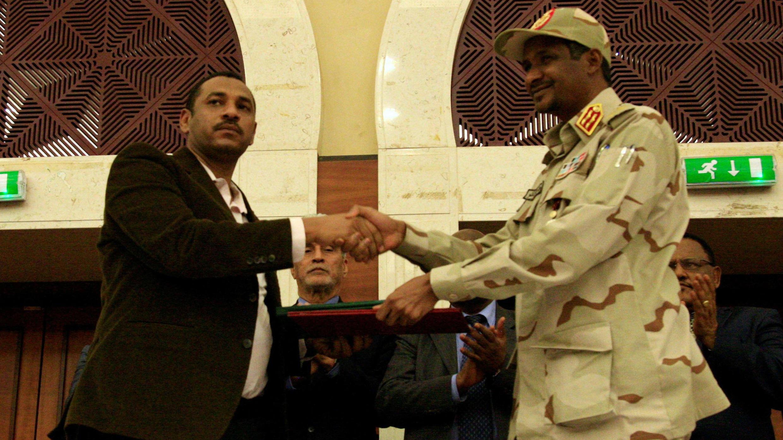 Los líderes de la junta militar y la oposición se dan la mano tras firmar un acuerdo de reparto de poder en Jartum, Sudán, el 17 de julio de 2019.