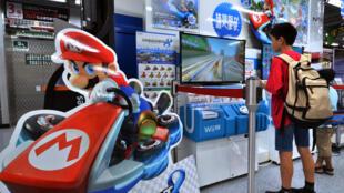 Un jeune tokyoïte s'amuse sur Mario Kart 8, le jeu phare de la Wii U de Nintendo.