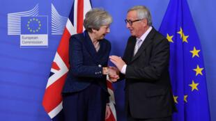 رئيس المفوضية الأوروبية جان كلود يونكر يصافح تيريزا ماي قمة بروكسل في 24 نوفمبر 2018.