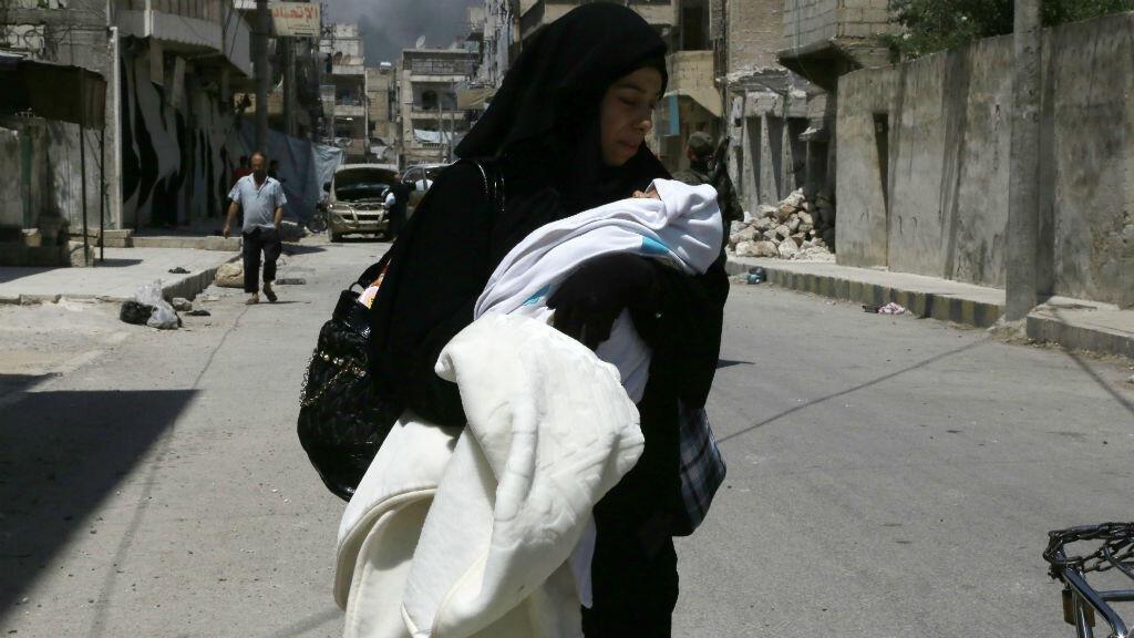 Une femme et son enfant arrivant à Minbej, le 13 août, après avoir été enlevés par le groupe EI.