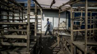 """Un homme marche dans un marché désert de la capitale Brazzaville lors de l'opération """"ville morte"""", le 29 mars 2016"""