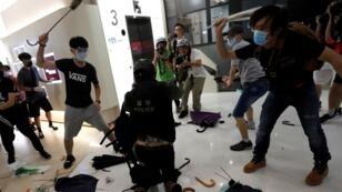 Manifestantes contrarios al Gobierno de Hong Kong hacen frente a un policía con paraguas en un centro comercial durante las protestas del domingo.