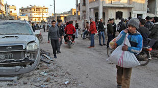 Civilians gather at the scene of an air strike by pro-regime forces in the town of Maarrat Misrin, in Syria's northwestern Idlib province, on February 25, 2020.