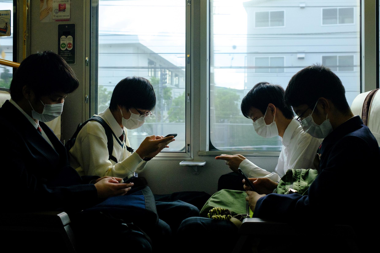 Cuatro estudiantes con mascarilla viajan en un tren en la estación de Kioto, el 21 de mayo de 2020.