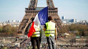 Manifestantes de los 'chalecos amarillos' miran hacia la Torre Eiffel durante la vigésima jornada de protestas del movimiento. París, Francia, el 30 de marzo de 2019.