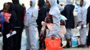مهاجرة إفريقية تنتظر أمام مركز احتجاز في تاجوراء في الضاحية الشرقية للعاصمة الليبية طرابلس، 5 ك1/ديسمبر 2017 لتلقي مساعدات قبل إجلائها