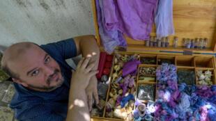 Mohamed Ghassen Nouira, artisan tunisien, près d'une boîte remplie de fils et de tissus teints en pourpre, dans son atelier à Tunis, le 11 juillet 2020