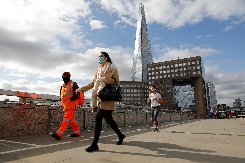 Transeúntes con máscaras en el Puente de Londres. Londres, Reino Unido, el 13 de mayo de 2020