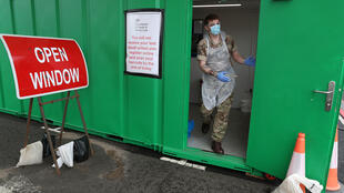 جندي يستعد لأخذ عينة لاجراء فحص للكشف عن كورونا المستجدّ في مطار غلاسغو في بريطانيا في 29 نيسان/أبريل 2020