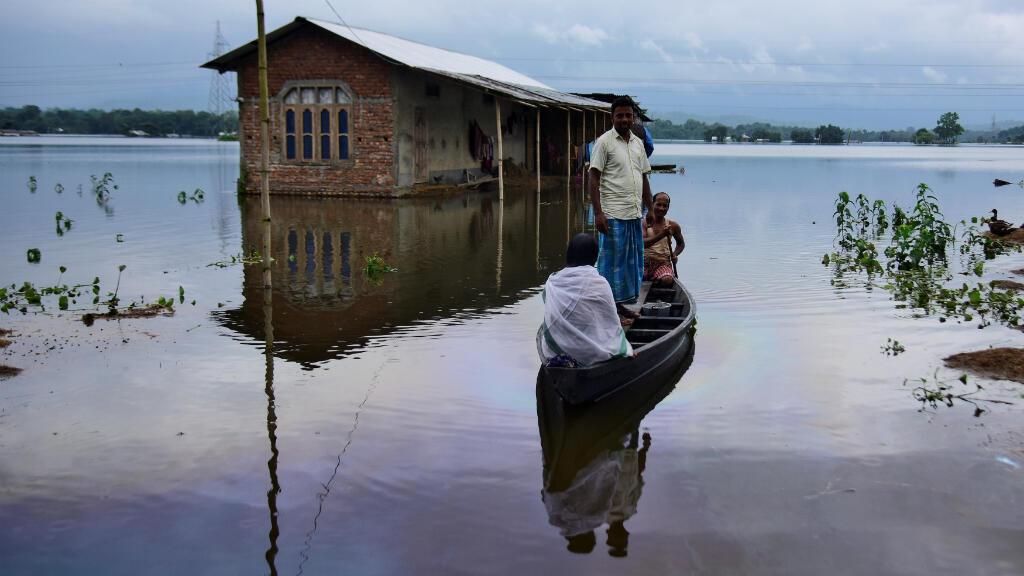 Civiles viajan en una balsa hacia un lugar seguro en un pueblo inundado en el distrito de Nagaon, en el estado nororiental de Assam, India, el 15 de julio de 2019.