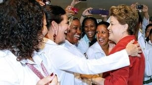 Then-president Dilma Rousseff of Brazil greets Cuban doctors after approving the More Doctors program with Cuba, in Brasilia on October 22, 2013