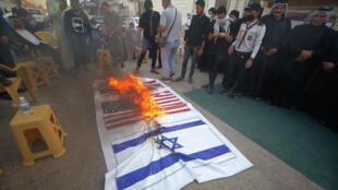 أنصار كتائب حزب الله العراقية المدعومة من إيران يقومون بحرق أعلام الولايات المتحدة وإسرائيل وبريطانيا في مدينة النجف، 18 سبتمبر/أيلول 2020.