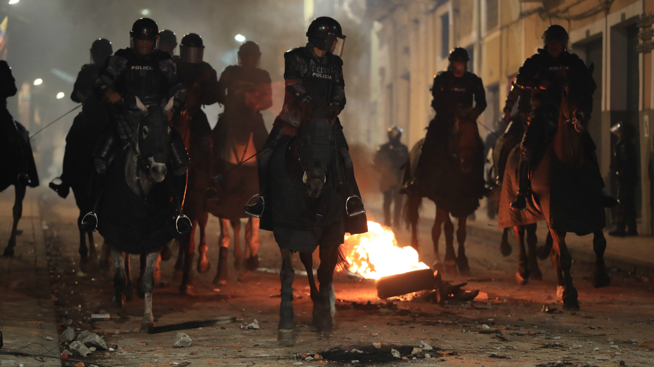 La policía cabalga junto a un neumático ardiendo durante la jornada de protesta contra las medidas económicas del Gobierno del presidente Lenín Moreno. En Quito, Ecuador. El 3 de octubre de 2019.
