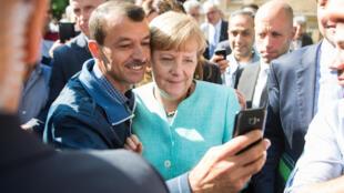 """Angela Merkel en pleine séance de """"selfie"""" avec un demandeur d'asile."""