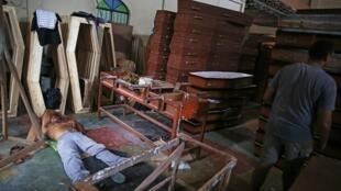 عامل يستريح في ورشة لصنع التوابيت في ماناوس بالبرازيل في 27 نيسان/أبريل 2020.