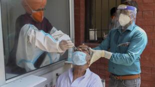 Les autorités sanitaires recueillent un échantillon d'écouvillon nasal d'un indien dans un hôpital civil à Amritsar le 24 août 2020