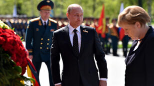Russian President Vladimir Putin and German Chancellor Angela Merkel take part in a wreath-laying ceremony at the Tomb of the Unknown Soldier by the Kremlin Wall in Moscow on May 10, 2015
