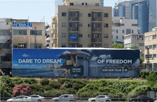 """لوحة إعلانية لمنظمة """"كسر الصمت"""" حولت شعار يوروفيجن """"تجرأ أن تحلم"""" إلى """"تجرأ أن تحلم بالحرية"""" قرب شارع مزدحم في تل أبيب في إسرائيل"""