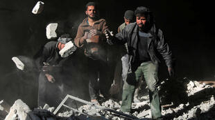 Des Syriens recherchent des victimes après les bombardements aériens qui ont touché Deir al-Asafir, à l'est de Damas, le 31 mars 2016.