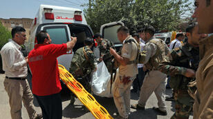 Les services de sécurité kurdes emportent le corps de l'un des assaillants de l'attaque contre le siège du gouvernorat d'Erbil, le 23 juillet 2018.