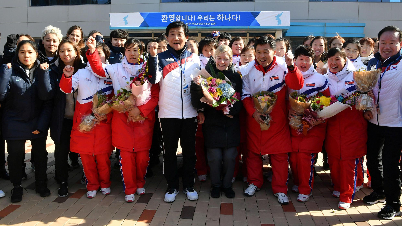 Las jugadores de hockey femenino de Corea del Norte y Corea del Sur posan con sus entrenadores el 25 de enero de 2018.