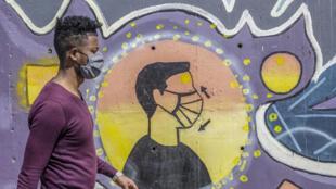 Un Éthiopien masqué passe devant une fresque enjoignant à porter le masque contre le Covid-19.