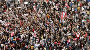 Los manifestantes hacen gestos mientras sostienen banderas libanesas durante una protesta por el deterioro de la situación económica, en Beirut, Líbano, el 18 de octubre de 2019.