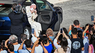 Pope Francis quickly removed his face mask as he emerged from his car