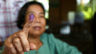 Una mujer camboyana muestra su dedo manchado con tinte después de votar durante las elecciones generales del país, en Phnom Penh, Camboya el 29 de julio de 2018.