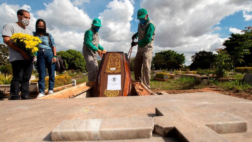 Funcionarios entierran a un fallecido por Covid-19 en un cementerio de Brasilia, la capital de Brasil, el 3 de junio de 2020.