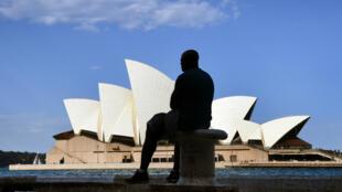 Une homme face à l'opéra de Sydney (2017).