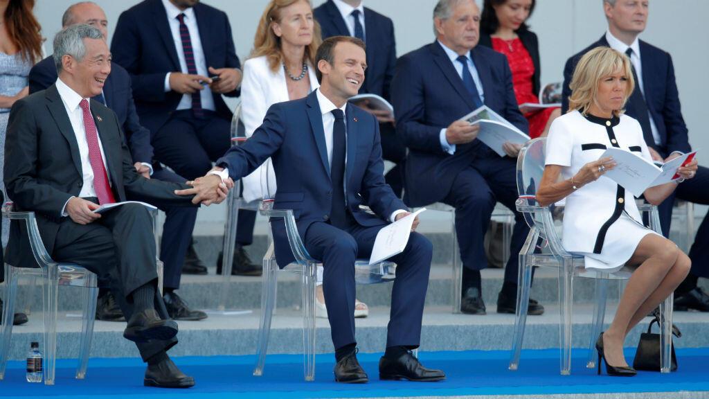 El mandatario francés, Emmanuel Macron,en compañía de su esposa, Brigitte Macron, y del primer ministro de Singapur, Lee Hsien Loong, durante el desfile militar del Día de la Bastilla en París, Francia, el 14 de julio de 2018.