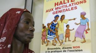 Une femme passe devant une affiche pour l'abolition des mutilations génitales féminines en Côte d'Ivoire, en 2005.