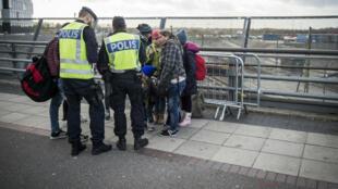 Des policiers contrôlent des réfugiés en gare de Malmö, en Suède, le 12 novembre 2015.