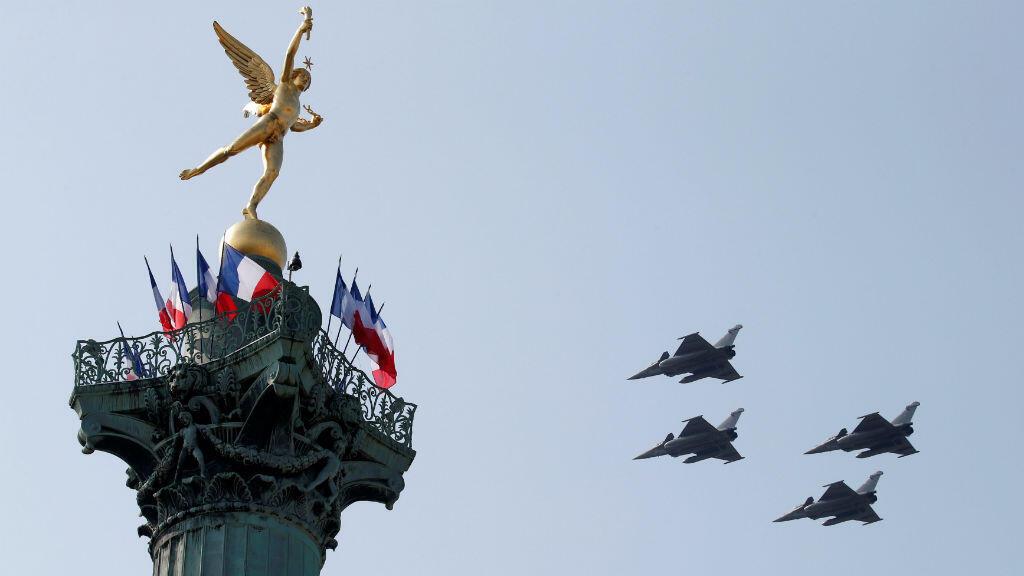 Cuatro de los aviones de combate que participaron en el desfile militar por el Día de la Bastilla, en cercanías al monumento al Genio de la Libertad, en París, Francia, el 14 de julio de 2018.
