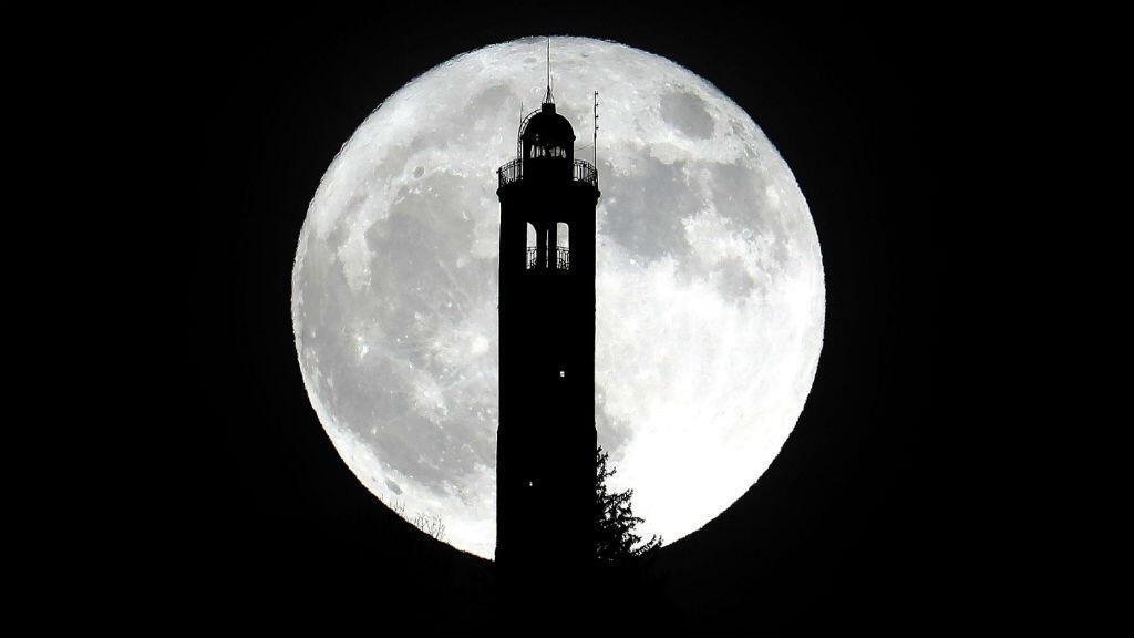 La silueta del faro de San Maurizio se dibujó a contraluz con el brillo de la Superluna en Brunate, Italia.